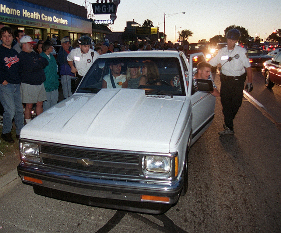 """. These unlucky Dream Cruisers get pulled over by police officers riding bicycles for \""""burning rubber\"""" along Woodward Avenue in Royal Oak Saturday night August 19, 2000. (Note the officer on the left with his hand on his gun.)"""