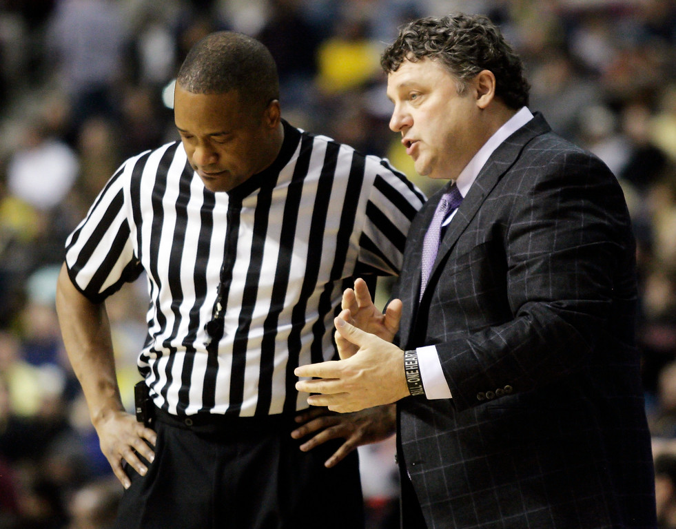 Description of . Oakland coach Greg Kampe, right, talks with official Earl Walton in the first half of an NCAA college basketball game against Michigan, Saturday, Dec. 10, 2011, in Auburn Hills, Mich. Michigan won 90-80. (AP Photo/Duane Burleson)