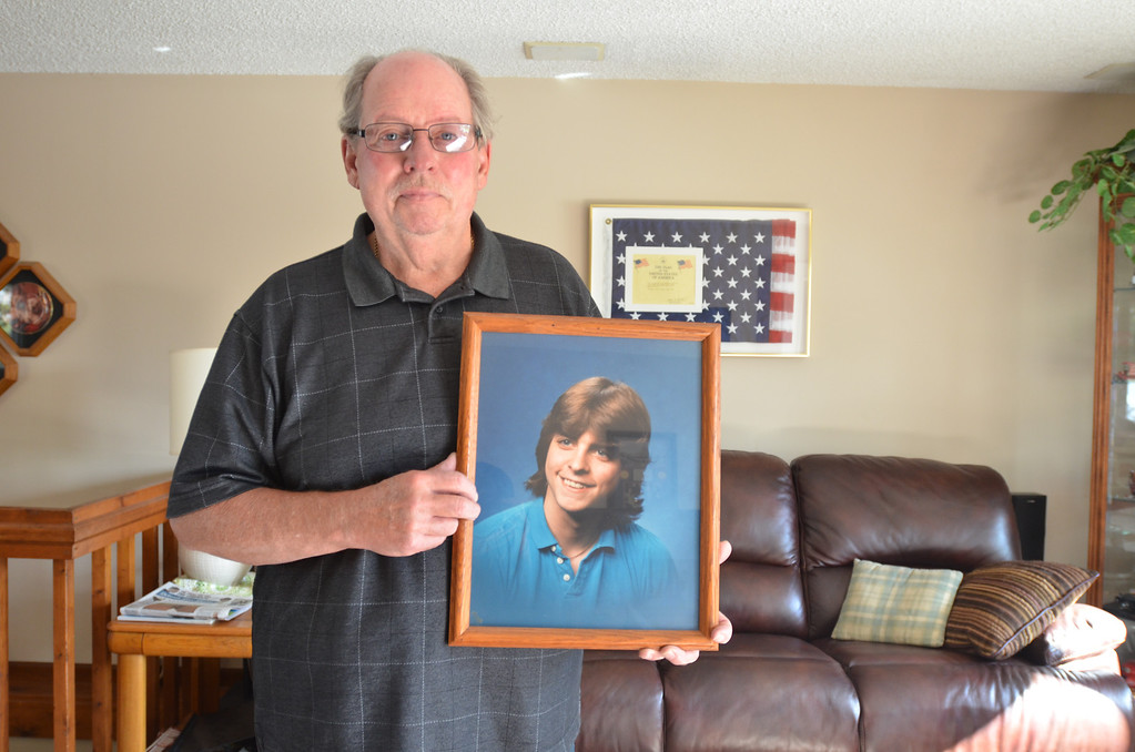 Description of . Robert Willett of Waterford Township displays a photo of his son, Kenneth Willett, who was killed in a car crash involving former Detroit Lions player Reggie Rogers, Oct. 20, 1988. The Oakland Press/AFTAB BORKA