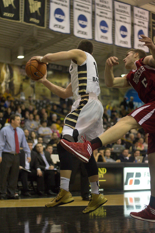 Description of . #13 Mitch Baenzinger grabs a rebound from a Rochester College player. Photo by Dylan Dulberg