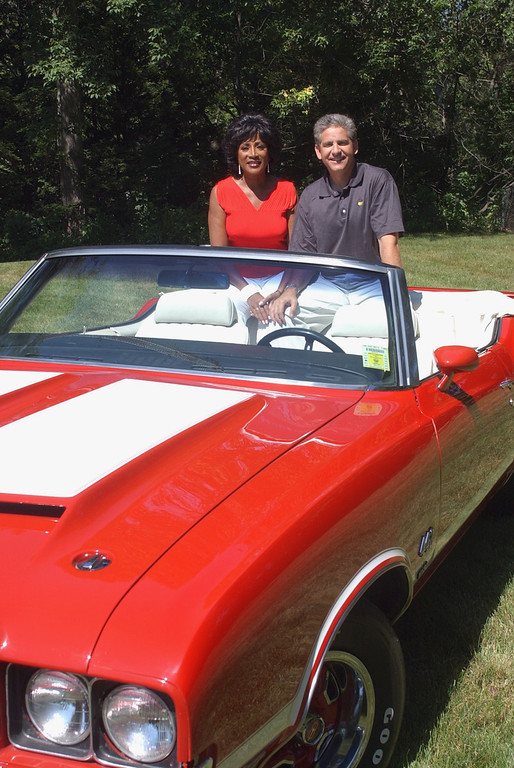 Description of . Diane Lewis and Guy Gordon from WXYZ-TV/channel 7 stand with a classic Oldsmobile for this year's  9th annual Woodward Dream Cruise.