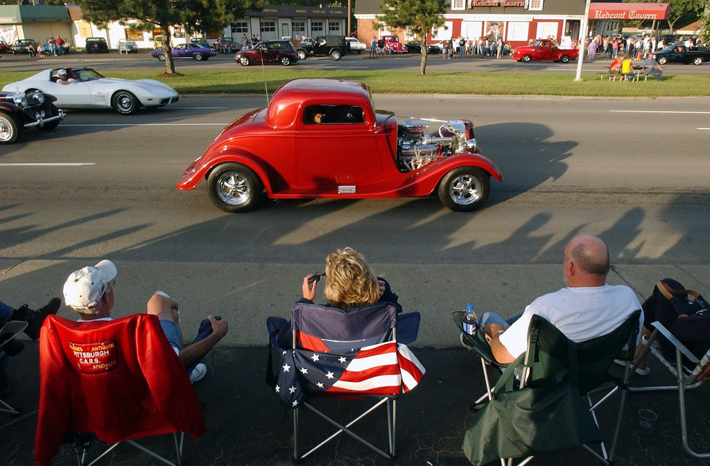 Description of . (L-R): Hud Hood, Shirl Millick, and Don Craig, all from Pittsburgh, PA, watch motorists drive south on Woodward Avenue towards 13 Mile Road, Thursday, August 19, 2004, in Royal Oak, Mich.