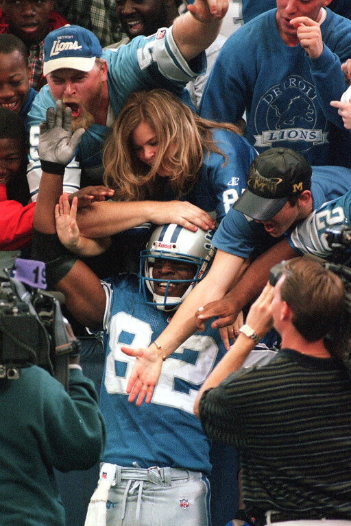 . Detroit Lions wide receiver Germane Crowell (middle, #82) leaps into the arms of fans after scoring a touchdown in the first quarter against the San Diego Chargers, Sunday, October 10, 1999.