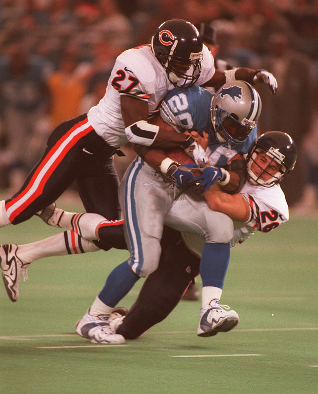 . Chicago Bear defenders #27 Walt Harris and #26 John Mangum try wrestling down Barry Sanders, who rushed for 167 yards on 19 carries.
