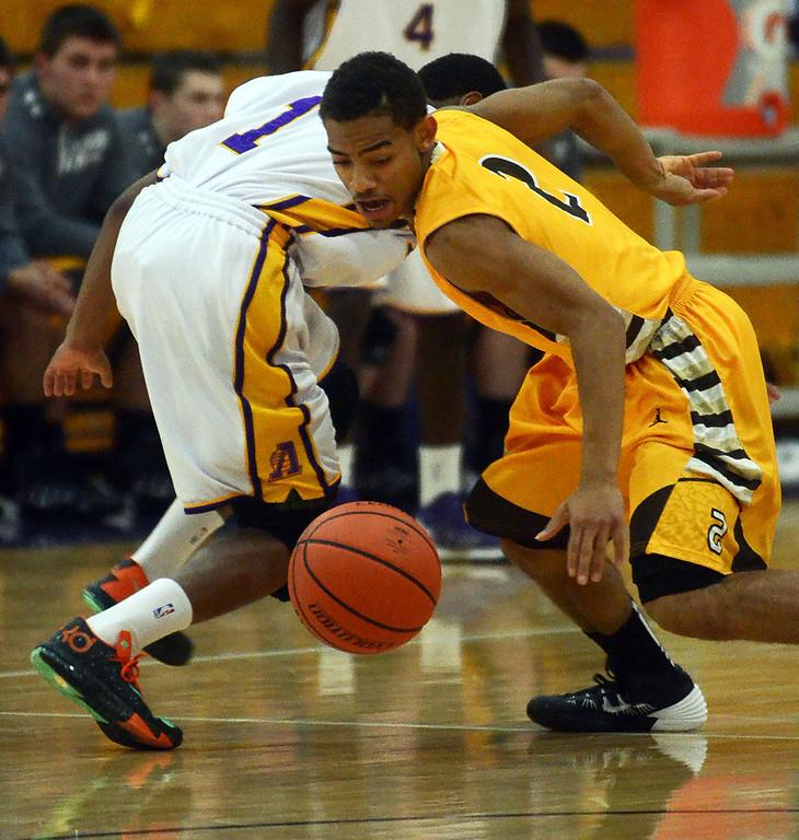 Description of . Rochester Adams #2 Akhemji Williams swipes the ball away from Avondale's #1 Zarrick Sturgis during their game at Avondale High School, Tuesday December 11, 2013. (Vaughn Gurganian-The Oakland Press)