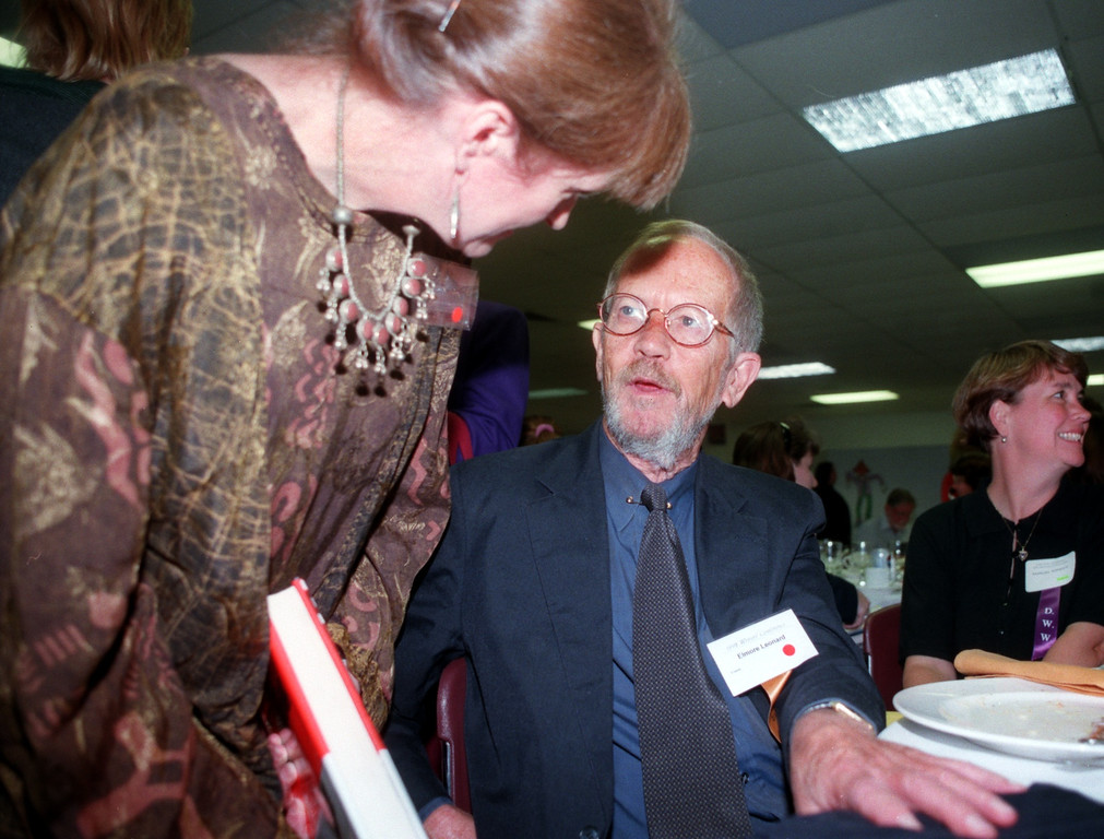 Description of . Novelist Elmore Leonard (right) talks with Mary Jo Firth Gillette, after signing one of his books for her, at the Oakland University 1998 Writers Conference luncheon.