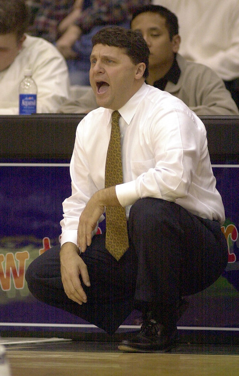 Description of . Oakland University men's basketball head coach Greg Kampe shouts instructions to his team as they played Cleveland State University during first half action, Saturday, December 9, 2000, at the O'rena in Rochester Hills, Mich.