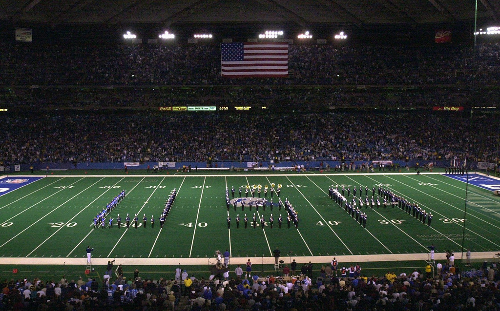 Description of . During pregame festivities of the Lions/Rams game, a marching band forms the letters