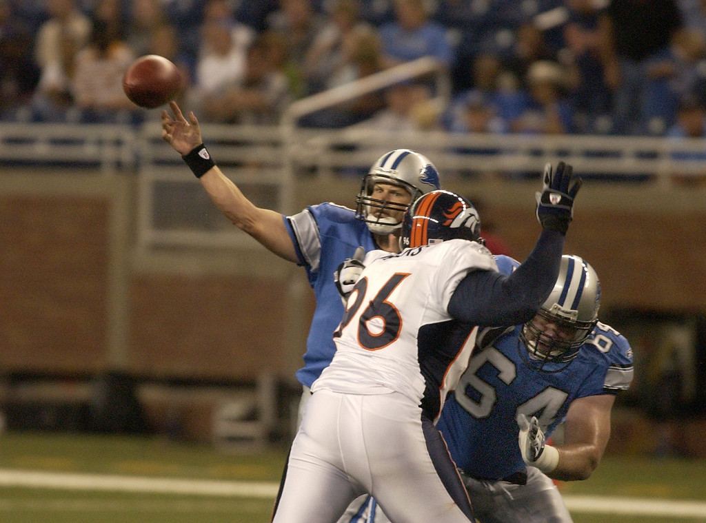 . Lions QB Jon Kitna tosses a short pass during first quarter action while Lions #64 Rick DeMulling holds off Bronco\'s #96 Michael Myers. The Oakland Press/DOUG BAUMAN