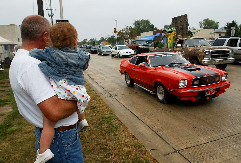 Description of . Stephen Parent of Commerce Township, Mich., holds his granddaughter, Brille (age 1), as they watch motorists make the loop on Woodward, during the Dream Cruise.  Photo taken on Saturday, August 21, 2010, in Pontiac, Mich.  (The Oakland Press/Jose Juarez)