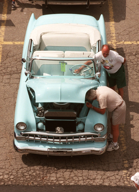 Description of . Ron Zilka (bottom) of Lake Orion, Mich.,  looks at the inside of his 1954 Chevy as his friend, Bud Barnard of Clarkston, helps him out, at the Phoenix Center parking lot in Pontiac, Mich., Saturday, August 21, 1999.