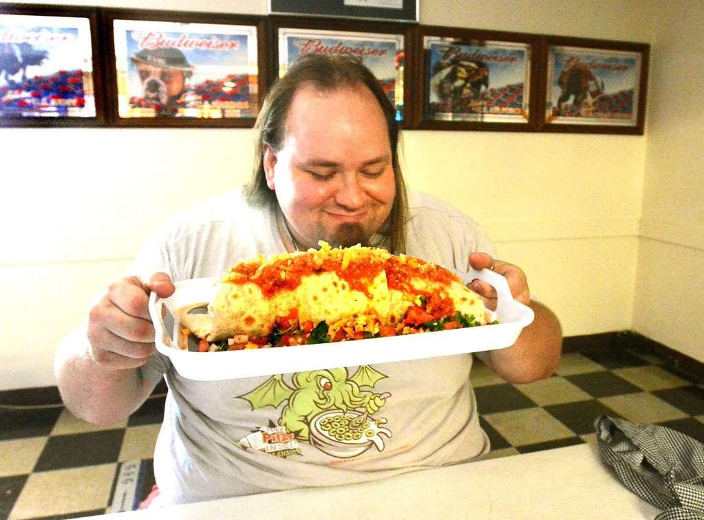 Description of . Tymm Earl of Waterford, with a giant, three pound burrito at VFW Post 1370 in Pontiac.  People have to pay $12 if they can't eat the entire burrito in 45 minutes. It's a way for the post to raise money.    Friday, July 19, 2013.  The Oakland Press/TIM THOMPSON