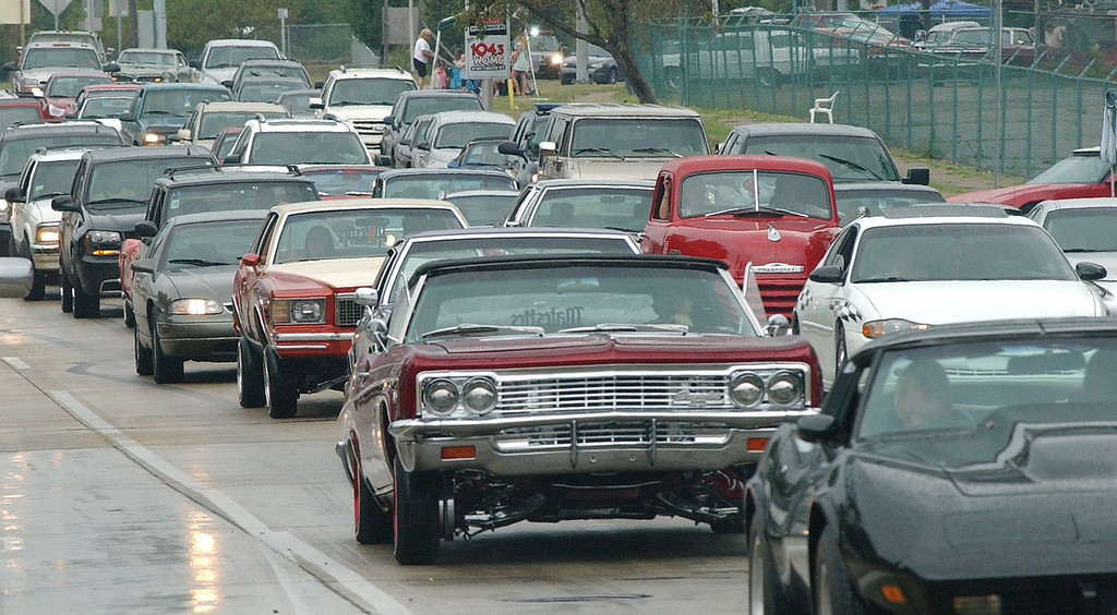 Description of . Motorists drive through the rain as they make the loop onto southbound Woodward, during the Dream Cruise.  Photo taken on Saturday, August 21, 2010, in Pontiac, Mich.  (The Oakland Press/Jose Juarez)