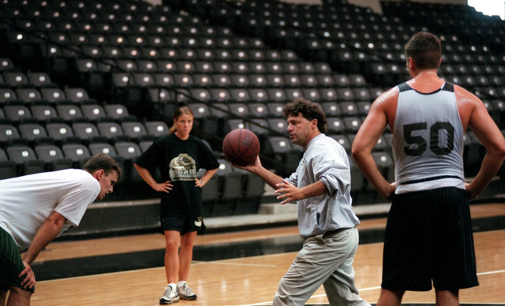 Description of . Jennifer Johntson, the new OU men's assistant basketball coach for coach Greg Kampe. She's the only female assistant coach in men's Division 1 basketball. Here she helps Greg work with Dan Champagne a Jr. from Linden, Mi.,  and Sebastien Bellin from Brussels, Belgium