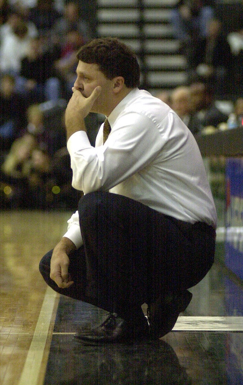 Description of . Oakland University men's basketball head coach Greg Kampe watches his team play Cleveland State University during first half action, Saturday, December 9, 2000, at the O'rena in Rochester Hills, Mich.