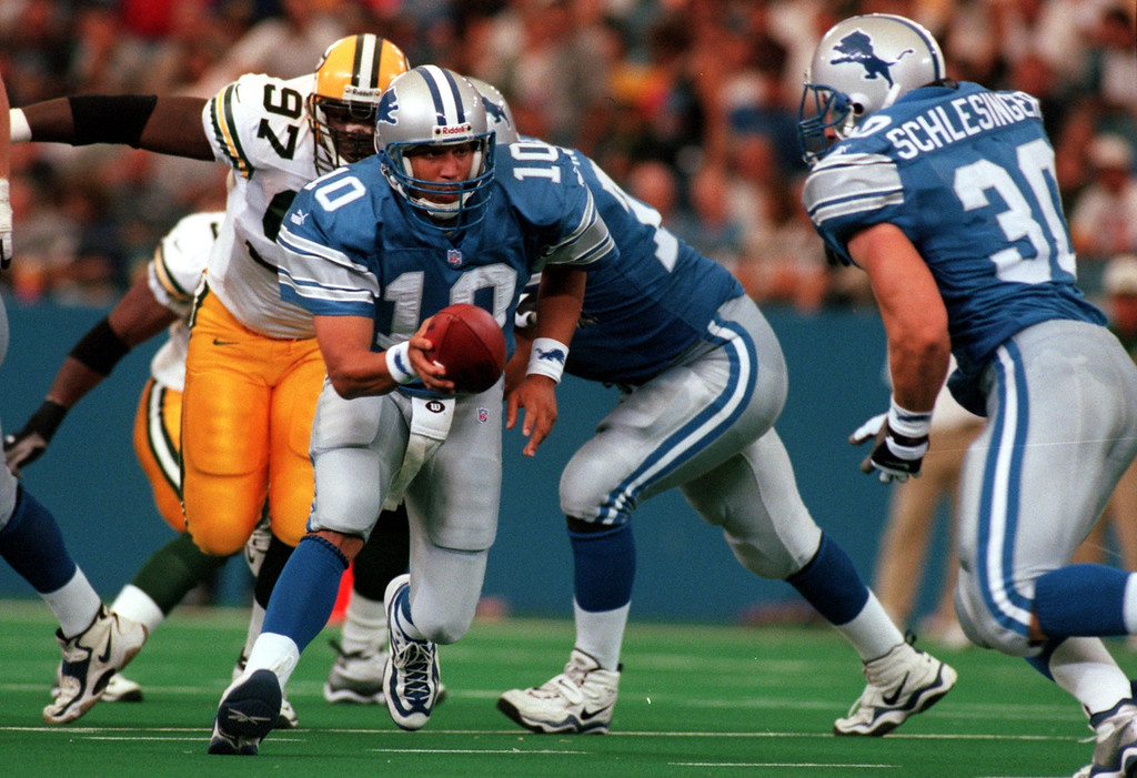 . Quarterback Charlie Batch (10) Detroit Lions hands the ball off to Cory Schlesinger (30) in the first half  during Sundays game against the Green Bay Packers at the Pontiac Silverdome Lions won 23-15 over Green Bay.