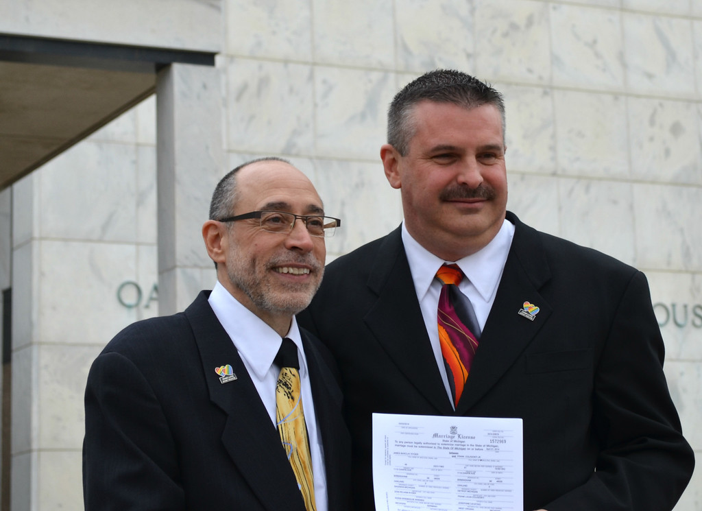Description of . Birmingham couple Frank Colasonti Jr., left, and James Ryder, right, in front of the Oakland County Courthouse after becoming the first couple to wed there Saturday morning after Michigan's same-sex marriage ban was struck down by a federal judge. Dustin Blitchok-The Oakland Press
