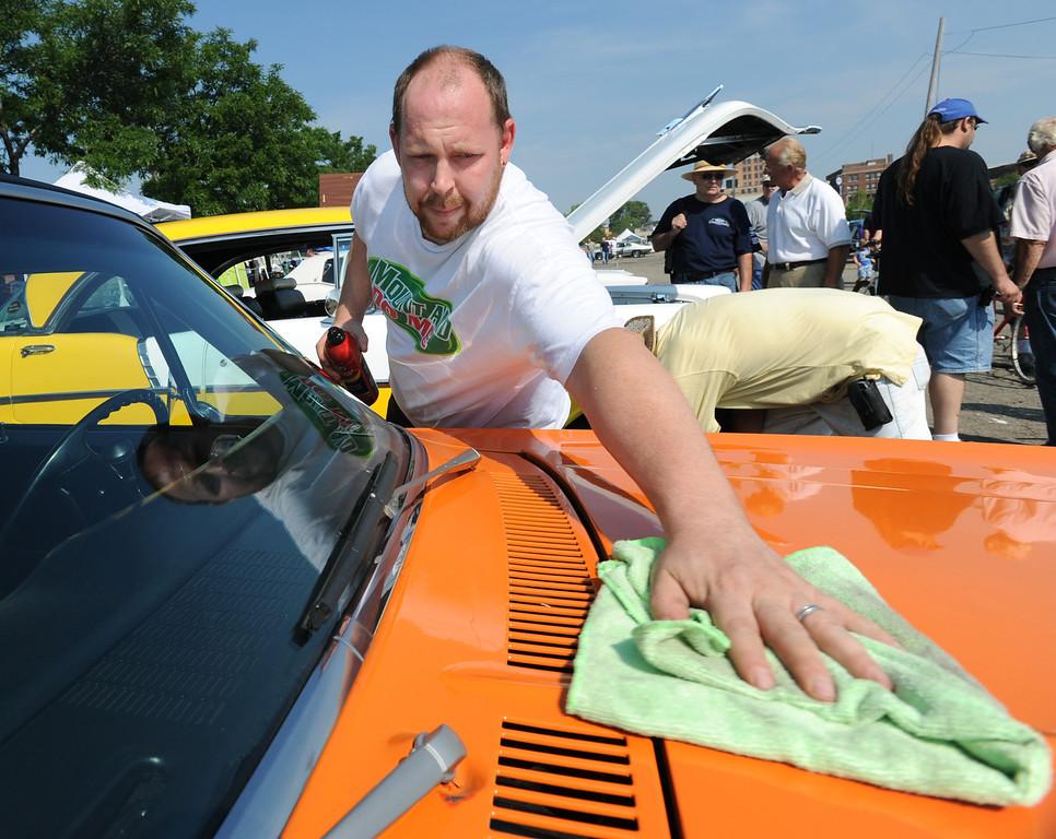 Description of . John Vanderpool of Pontiac, Mich., shines his 1972 Chevy Nova in Lot 9, Saturday, August 15, 2009, in Pontiac, Mich.  (The Oakland Press/Jose Juarez)