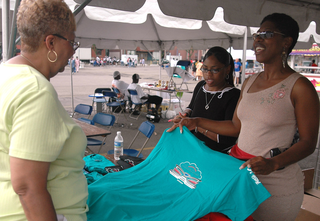 Description of . Milie Naylor buys shirts for her grandchildren from Jackie Phlegm who was selling shirts for the 2003 Dream Cruise at the Pontiac Soul Festival Saturday afternoon.     Photographed Saturday, July 17, 2004.