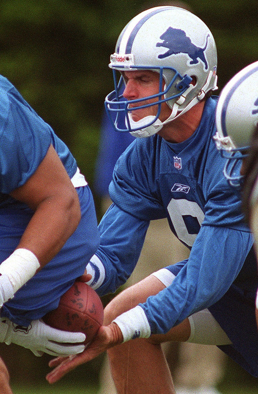 . Detroit Lions quarterback Jim Harbaugh, who used to play for Michigan, takes the handoff during a recent practice at the Pontiac Silverdome.