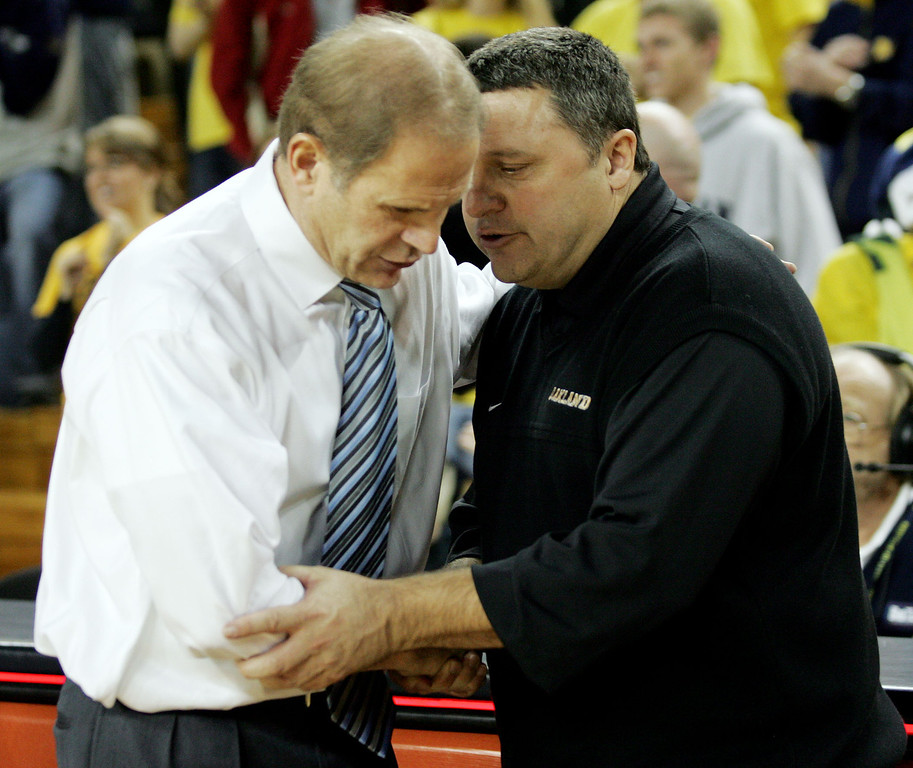 Description of . Michigan head coach John Beilein, left, shakes hands with Oakland head coach Greg Kampe, after a college basketball game, Wednesday, Dec. 12, 2007, in Ann Arbor, Mich. Michigan won, 103-87. (AP Photo/Tony Ding)