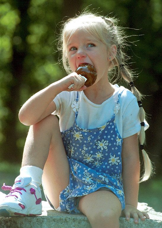 Description of . Millina Kacmar, 4, of Eastpointe, enjoys a caramel apple at Yates Cider Mill in Rochester Hills Friday.