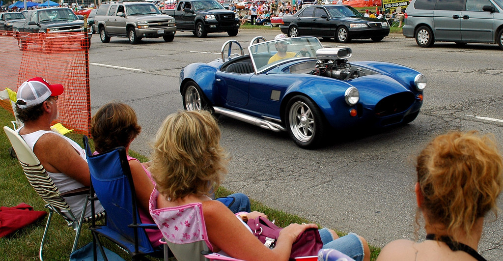 Description of . Spectators sit along Woodward Ave. Saturday afternoon watching the Woodward Dream Cruise.