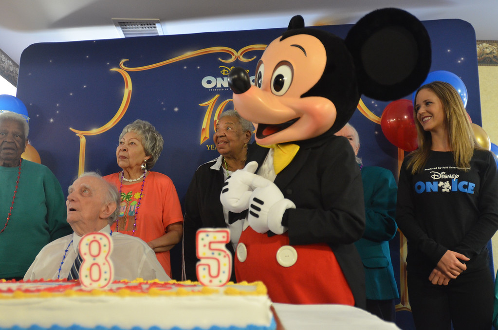 Description of . Mickey Mouse, along with several 85-year-old metro Detroiters, is listening to the birthday song at a party organized by Disney On Ice at American House Southfield Senior Living in Southfield.