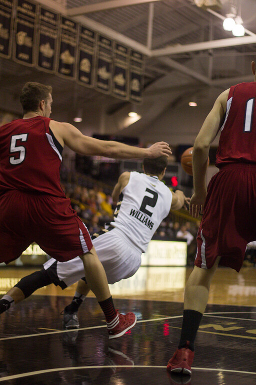 Description of . Williams falls while attempting to pass the ball to Bader. Photo by Dylan Dulberg
