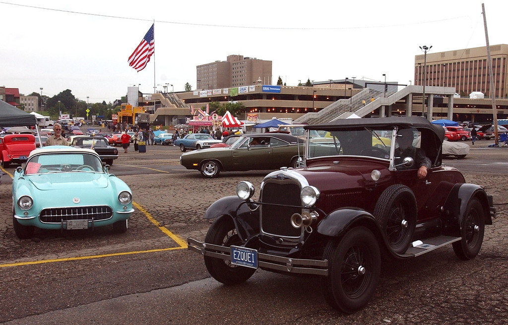 Description of . A vintage car looks for a parking spot past a classic Corvette, left, on display in the parking lot of the Phoneix Plaza in downtown Pontiac during Friday night\'s Woodward Dream Cruise. The annual classic cruise goes from Pontiac to Ferndale covering 16-miles of classic cars, food & entertainment along the way.