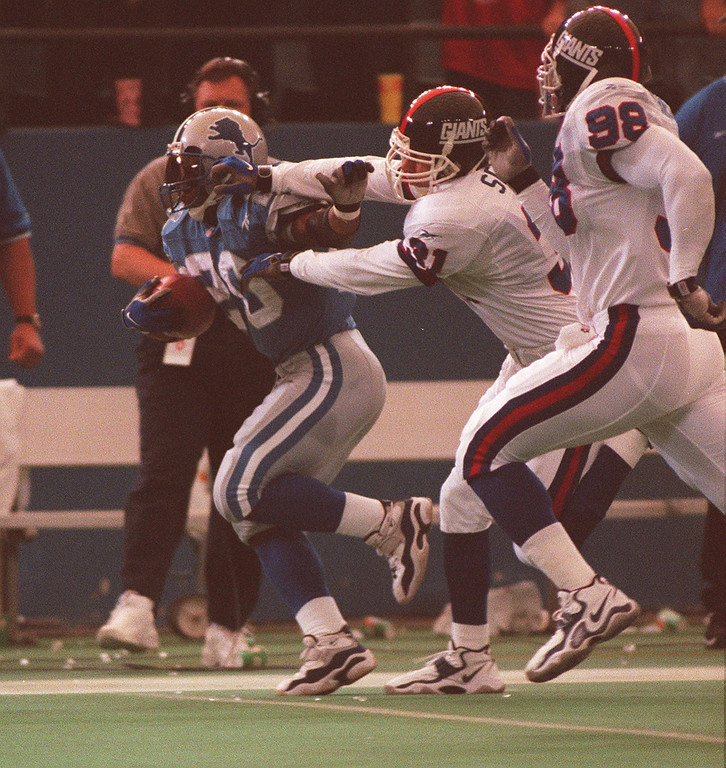 . Lions Barry Sanders gets tackled after a big gain by New York Giants # 31 Jason Sehorn and #98 Jessie Armstead.