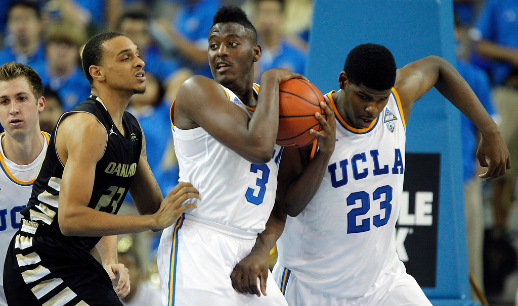 Description of . UCLA guard Jordan Adams (3) pulls down a rebound between Oakland forward Tommie McCune, left, and UCLA's Tony Parker, right, during the second half of their NCAA college basketball game Tuesday, Nov. 12, 2013, in Los Angeles. UCLA won 91-60. (AP Photo/Alex Gallardo)