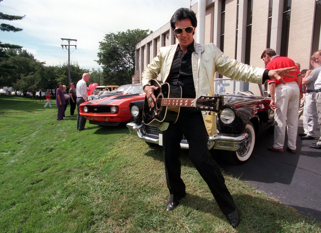 Description of . Elvis impersonator Dave King with some of the cars taking part in this year\'s Woodward Dream Cruise, on display at Eaton Corp.\'s employee Dream Cruise picnic in Southfield.