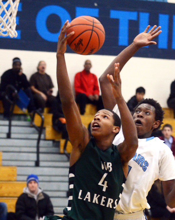 Description of . West Bloomfield's #4 Trishton Jackson goes up for a layup that gets blocked by Waterford Mott's #11 Austin Sherrell during their game at Waterford Mott High School, Thursday December 12, 2013. (Vaughn Gurganian-The Oakland Press)