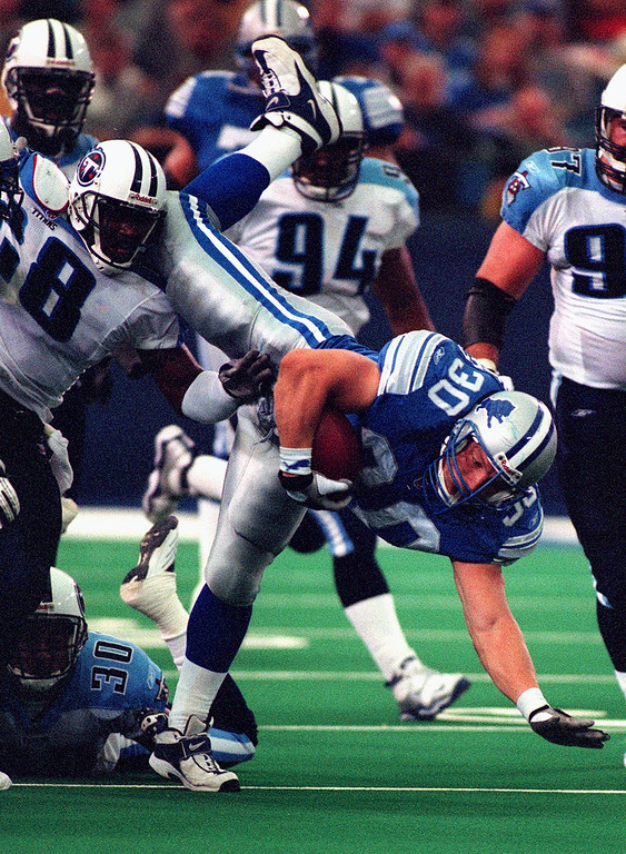 . Detroit Lions Fullback Cory Schlesinger (right) scrambles for yardage past Tennessee Titans Aric Morris (left #28) and Donald Mitchell (left #30)  in the Lions 27-24 loss at the Pontiac Silverdome Sunday.