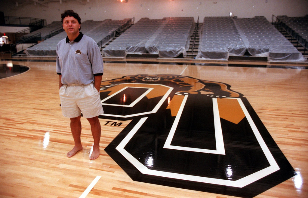 Description of . Oakland University men's basketball head coach Greg Kampe at center court of the then-new basketball court at the Athletics Center O'rena. The facility, which opened November 16, 1998, signified the school's ascension to Division I athletics.