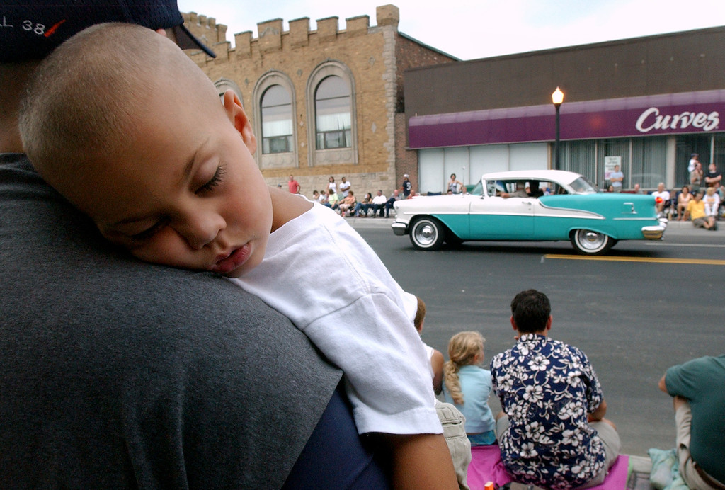 Description of . Nicholas Marchese, age 3, of Cleveland, Ohio, sleeps on his dad's shoulder, oblivious to the loud cars motoring westbound along12 Mile Road, during a car parade in downtown Berkley.  Marchese's dad said he, his wife, and son were in the Detroit area to visit friends, and that they had to partake in Dream Cruise events.  Photo taken on Friday, August 18, 2006, in Berkley, Mich.  (The Oakland Press/Jose Juarez)