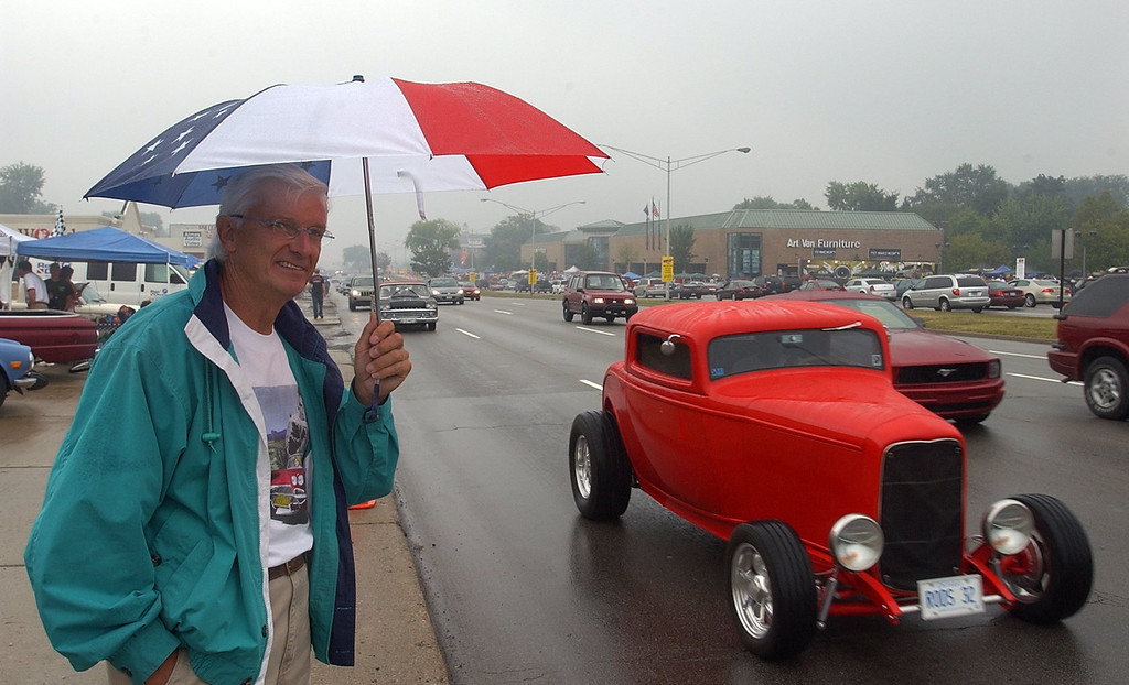 Description of . John Schinella, of Orchard Lake, watches the classic cars cruise Woodward Ave. in Royal Oak in the rain during the 2006 Woodward Dream Cruise.