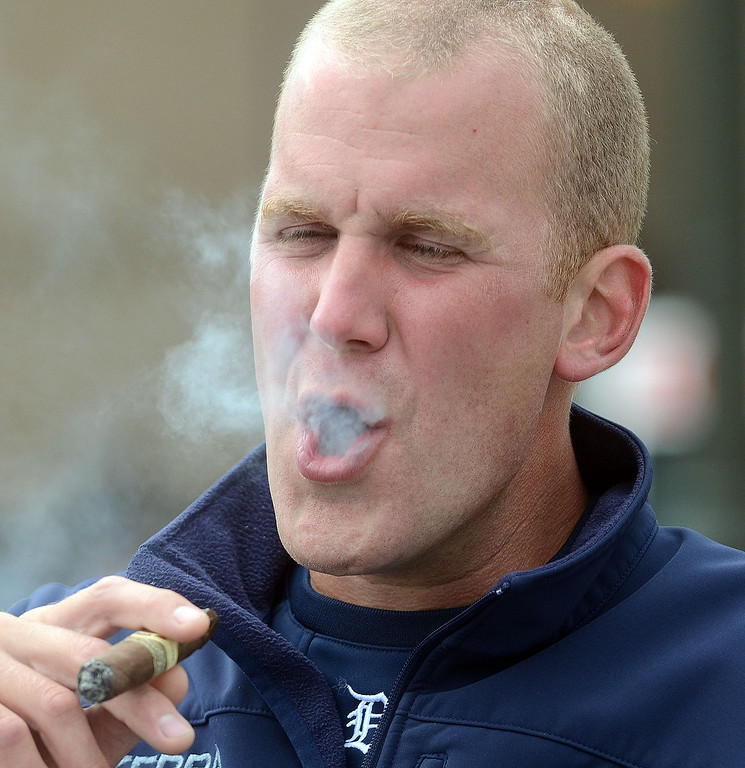 Description of . Robert Marcis, of Troy, enjoys a pregame cigar before heading into Comerica Park for the start of Game 3 of the ALDS between the Tigers and Oakland A's, Monday October 7, 2013. (Oakland Press Photo:Vaughn Gurganian)