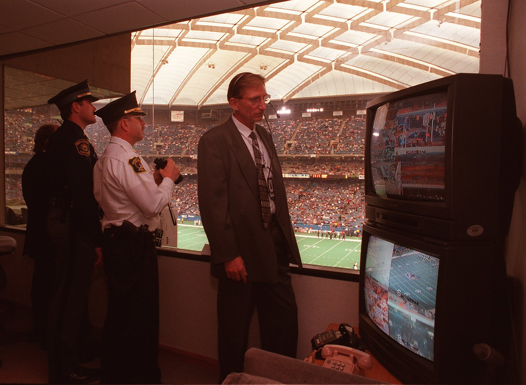 Description of . (f.left) Michigan State Police Officer Dennis MacDonell, Pontiac Police Capt. Pat McFalda and Rick Nosek, Director of Silverdome Security, keep an eye on the crowd during the Lions/Bears game.