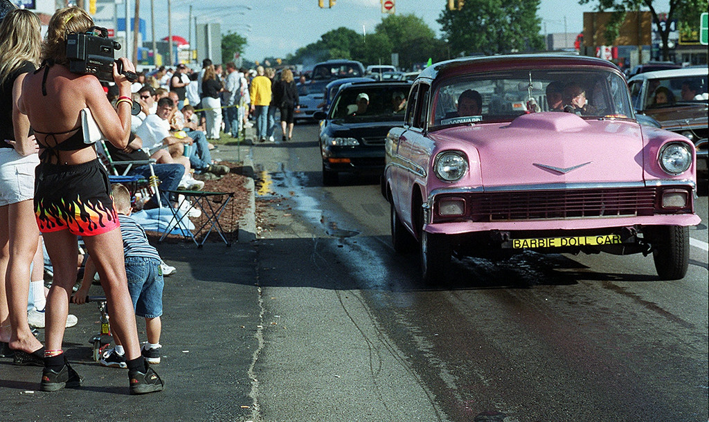Description of . Brenda Oldeck (left) videotapes the parade of cars up Woodward including this pink Chevy Bel Air during the Dream Cruise 2000 saturday afternoon.