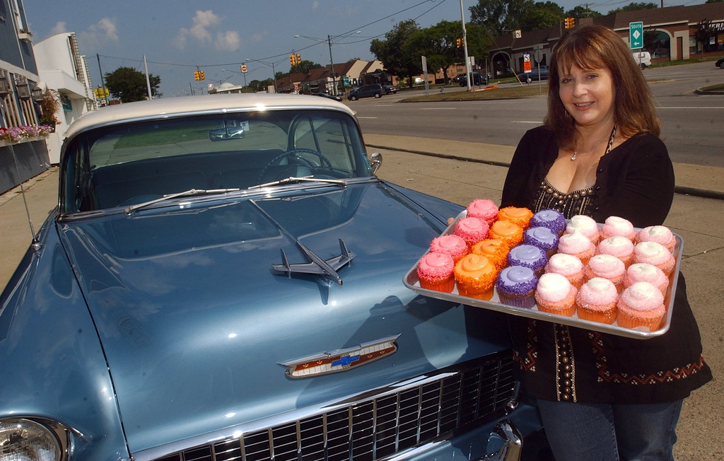 Description of . Pam Turkin, owner of Just Baked cupcakes in Royal Oak, with Faygo red pop, orange pop, grape pop and Pink Cadillac cupcakes for this Saturday\'s Woodward Dream Cruise.