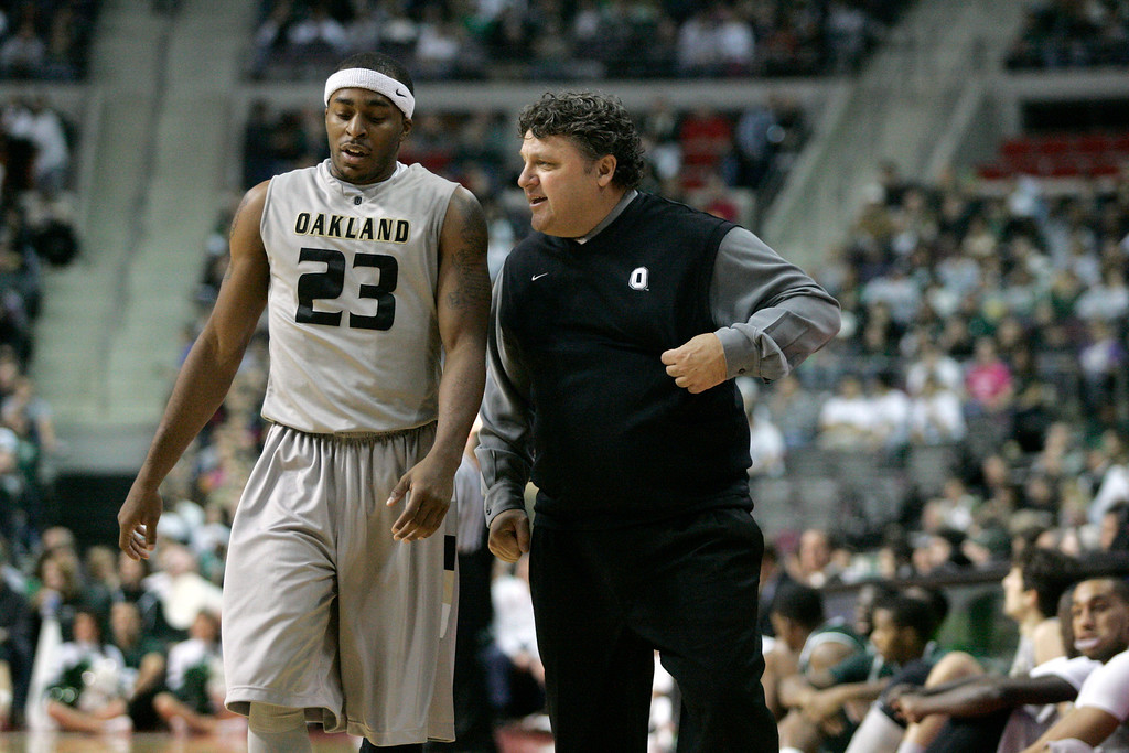 Description of . Oakland coach Greg Kampe, right, talks with guard Reggie Hamilton (23) in the first half of a NCAA college basketball game against Michigan State Saturday, Dec. 11, 2010, in Ann Arbor, Mich. (AP Photo/Duane Burleson)