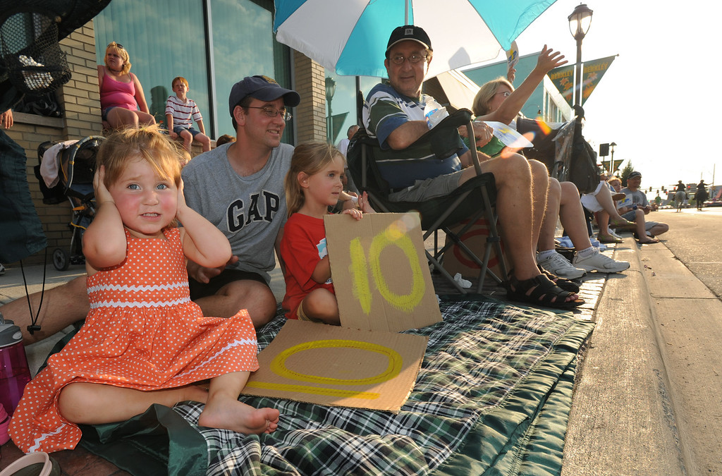 """Description of . Amelia Guccione (far left, age 2) covers her ears after a car had revved its engine. Amelia and her family (L-R): Grace Guccione, age 5; Joe Guccione, Joe Guccione Sr., and Kathy Guccione, were holding up signs, showing the numeral \""""10\"""", to show their support of the cars that were parading past them.  Photo taken during the Berkley CruiseFest, Friday, August 14, 2009, in Berkley, Mich.  (The Oakland Press/Jose Juarez)"""