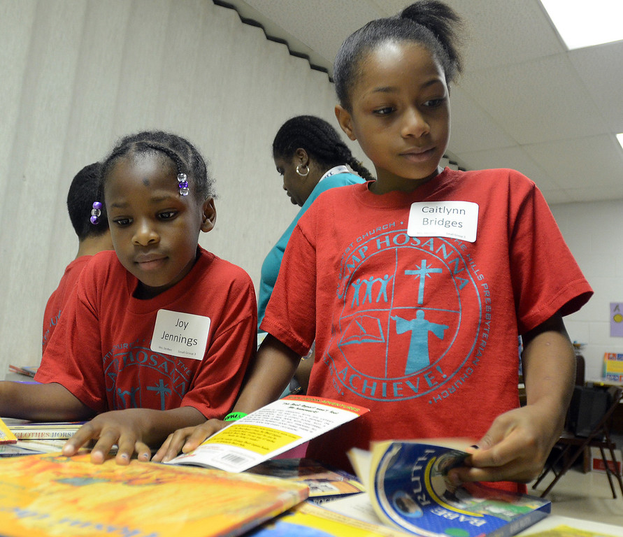 Description of . Joy Jennings, 7 (left) and Caitlyn Bridges, 8, look through books to read during the free Camp Hosanna at New Bethel Missionary Baptist Church in Pontiac, Monday July 22, 2013. (Oakland Press Photo:Vaughn Gurganian)