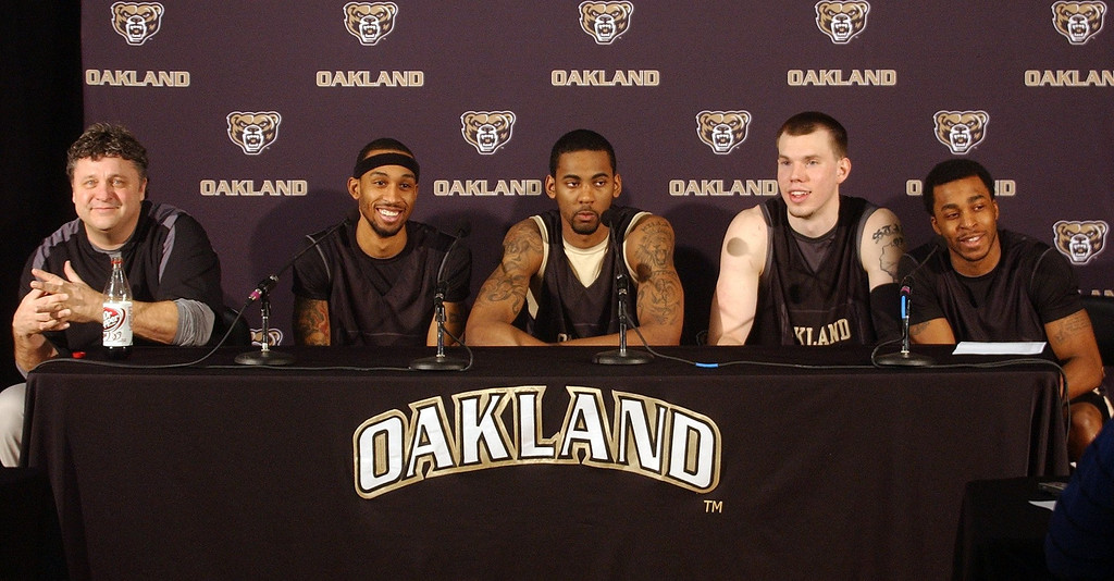 Description of . (from left) Greg Kampe, Oakland University Mens Basketball Head Coach and players Larry Wright, Keith Benson, Will Hudson and Reggie Hamilton share a lighter moment during a press conference at the O'rena at Oakland University in Rochester Hills. The team plays this weekend in the 2011 Summit League Men's Basketball Championship in Sioux Falls, South Dakota. (Oakland Press Photo/Vaughn Gurganian)