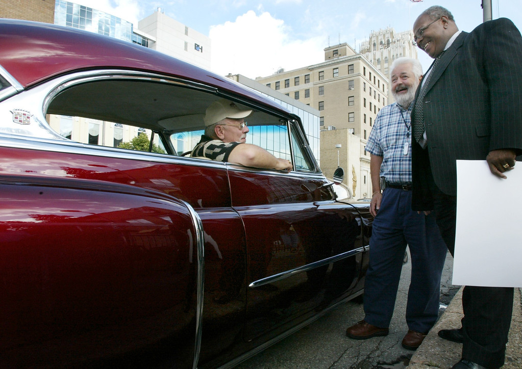 Description of . Bill McIninch of Groveland Township sits in his 1952 50th Anniversary Cadillac in front of Bo\'s Brewery and Bistro in Pontiac while talking to Bo Young (owner of Bo\'s) of Troy and Pastor Douglas Jones of West Bloomfield (President of Woodward Dream Cruise Inc.) before a Downtown Business Association meeting. Photographed Wednesday, August 4, 2004.