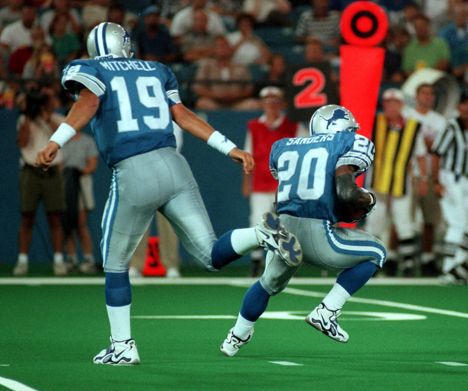 . Detroit Lions quarterback Scott Mitchell (19) hands the ball off to Barry Sanders during the first quarter against the Arizona Cardinals of the preseason home opener.