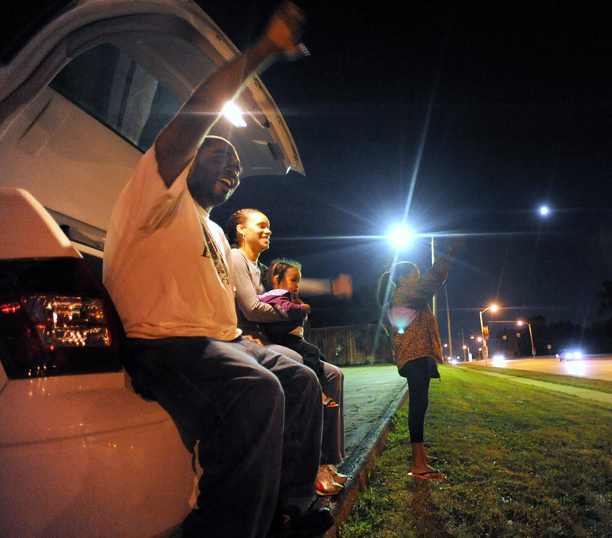 """Description of . Robert Cato, foreground, of Pontiac, Mich., and his family (L-R): Cianna Cato, age 2; Janell Cato; and Halaya Cato, age 9, watch cars begin their turn on the Loop, along northbound Woodward Avenue.  The Cato family, who watched from the back of their vehicle in the parking lot of St. Vincent De Paul Catholic Church, watched cars from about 8:30 pm to 10:30 pm.  The reason they came out to watch the cars three days before the actual Dream Cruise was because, according to Robert, it was Halaya\'s idea to watch the cruisers at night.  Halaya also wanted to count how many \""""yellow cars\"""" passed them by.  Photo taken on Wednesday, August 18, 2010, in Pontiac, Mich.  (The Oakland Press/Jose Juarez)"""