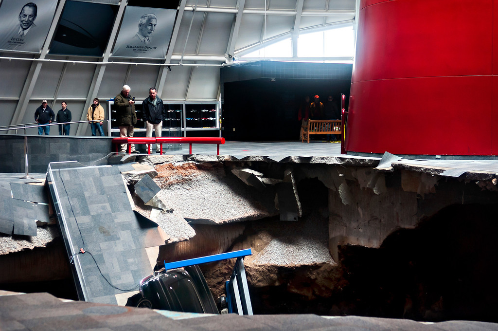 Description of . Officials view a sinkhole that opened up in the Skydome showroom, Wednesday, Feb. 12, 2014, at the National Corvette Museum in Bowling Green, Ky. Eight display cars were swallowed by the hole. (AP Photo/Daily News, Miranda Pederson)